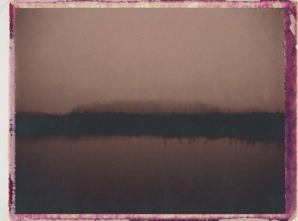 sepia-toned photograph of water with a dark band and then a hazy mound in the distance